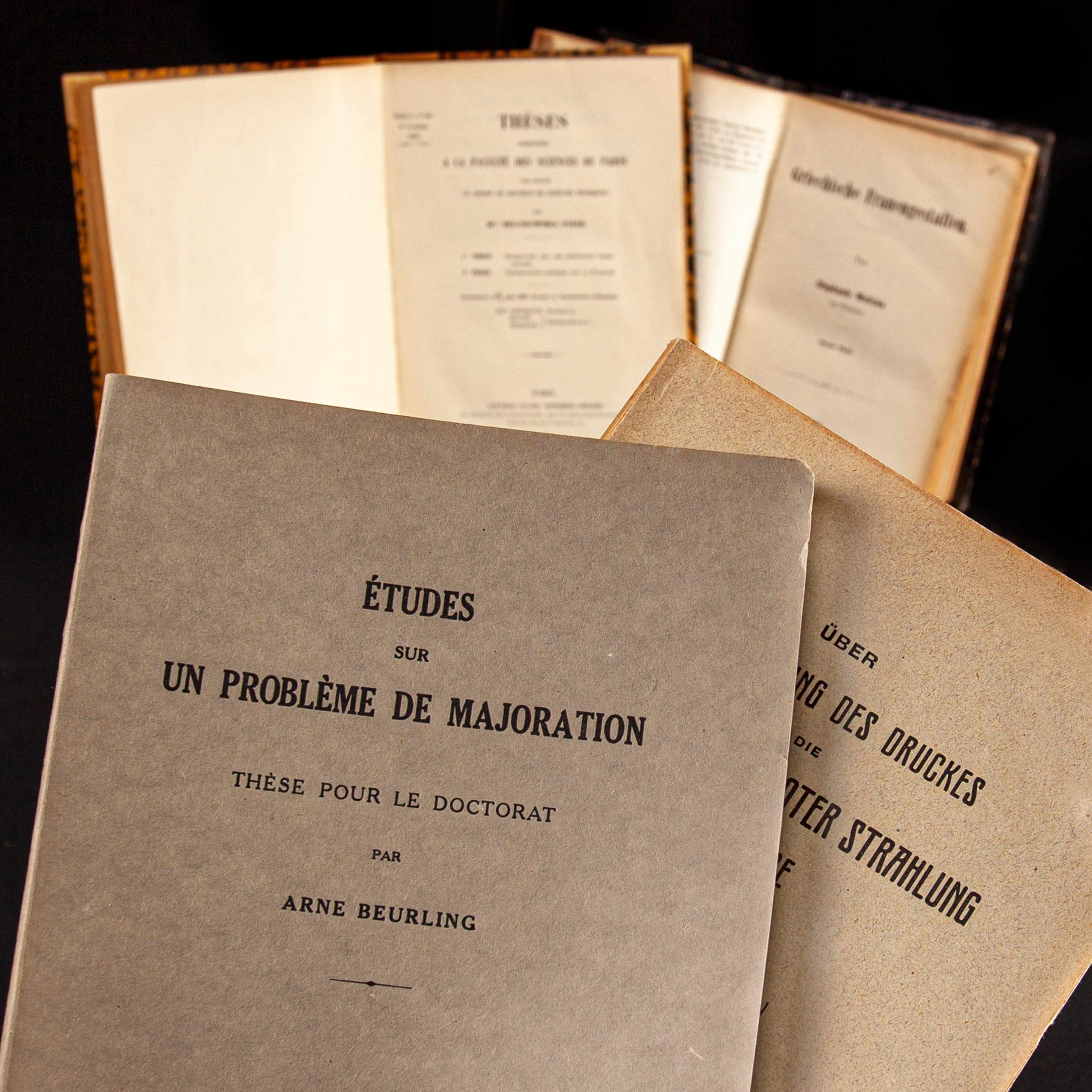 Grey and brown volumes containing scientific dissertations