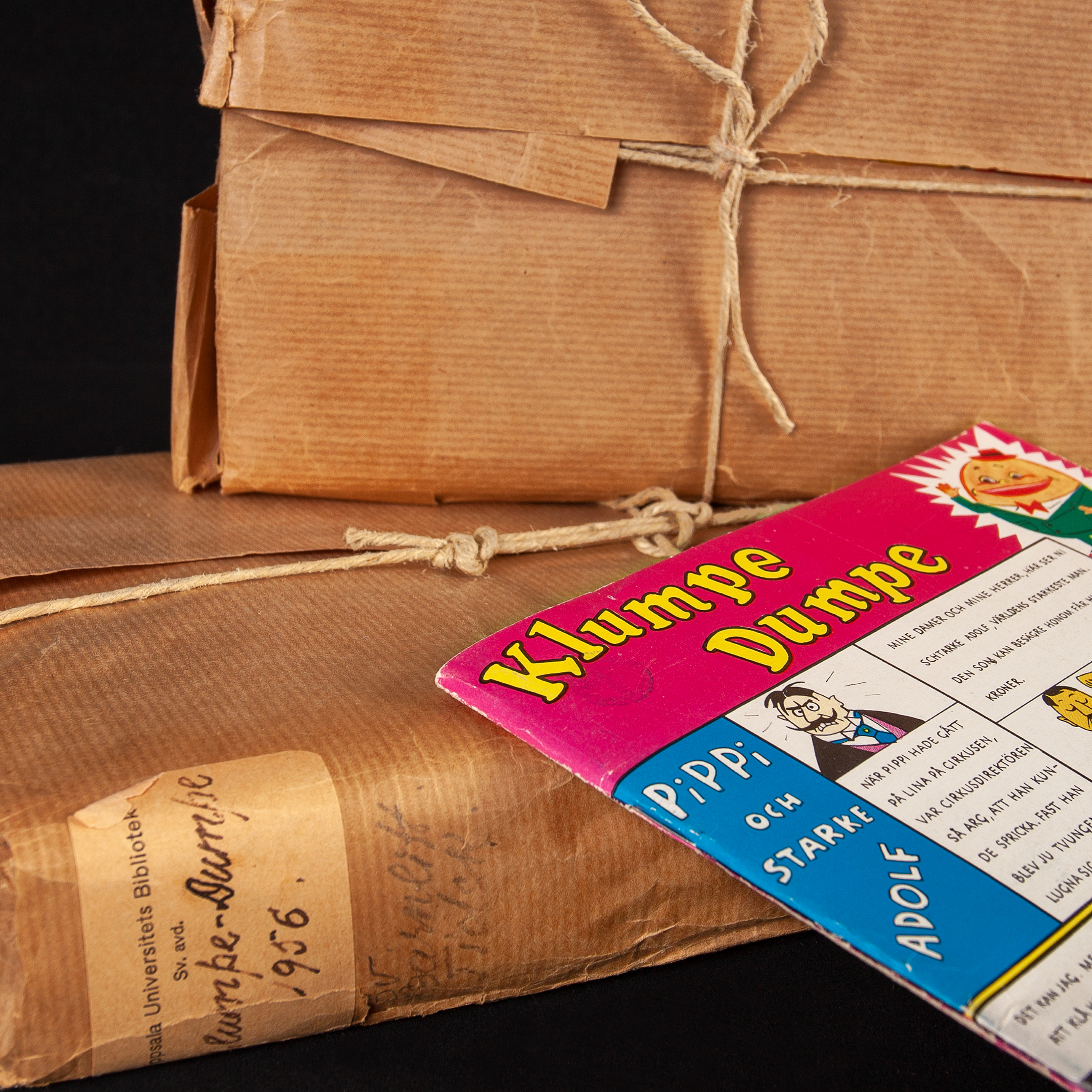 Comics are peaking out of a brown paper parcel  bound with string